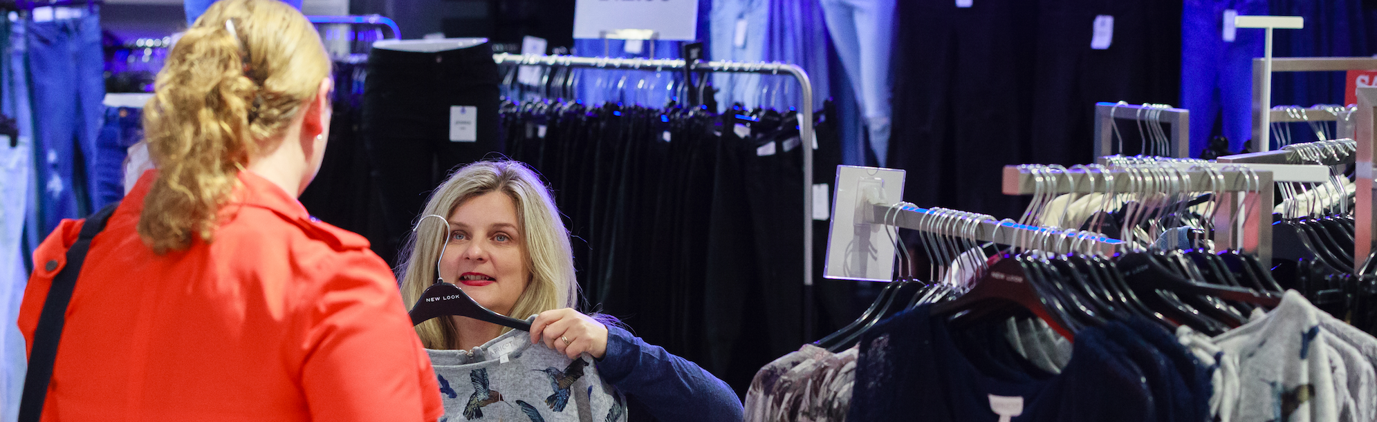 A photograph of Caroline Macdonald in a clothes shop. Caroline is holding up a top.