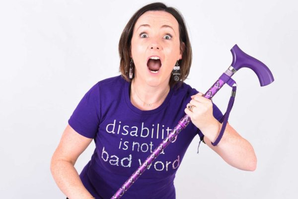 Lisette in a purple t-shirt which reads 'disability is not a bad word', holding her purple walking stick with her eyes and mouth wide open