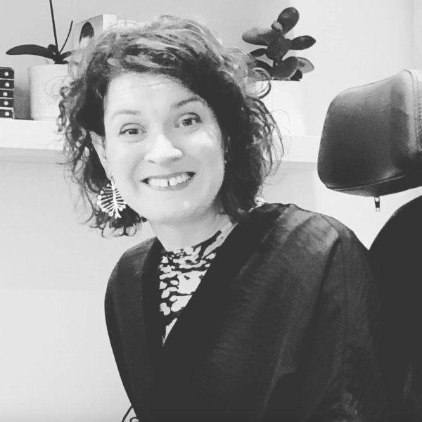 Image description: Black and white image of Lucy facing the camera and smiling. Lucy has short, dark, curly hair and she is wearing some dangle earrings. She has on a patterned blouse and a dark coloured cardigan. Behind her is a shelf with various potted plants on top.