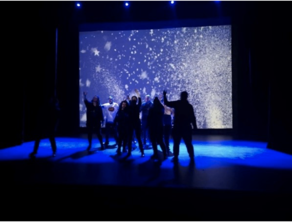 Image Description: Full Circle Theatre Company performance photo from their stage production of In The Middle of Our Street. There are silhouettes of ten learning disabled performers with one arm in the air, gently swaying, in a deep blue light, with a back projection of stars and a confetti explosion. It suggests a party or festival atmosphere.
