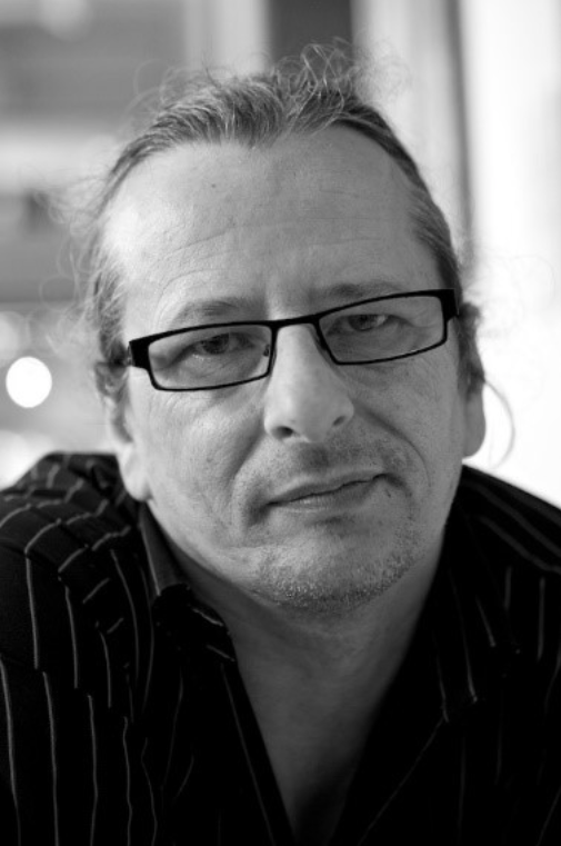 Image Description: A black and white photograph of Kev Howard facing the camera head on and smiling. He is wearing rectangular black rimmed glasses and a black shirt.