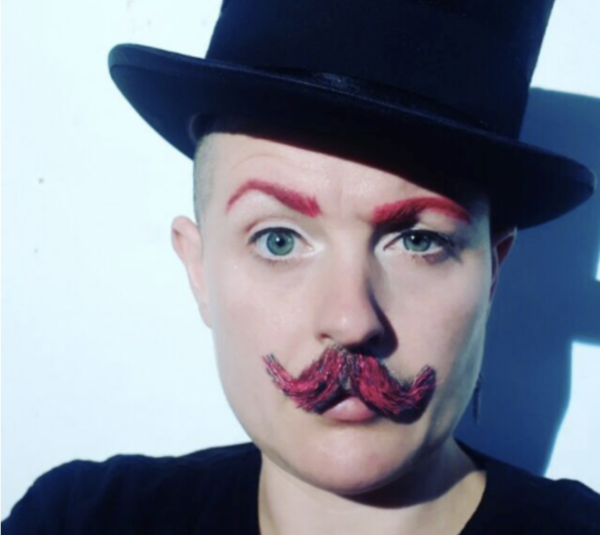 Image Description: A photo of Lady Kitt facing the camera head on, wearing a black top hat and a pinky/brown moustache, their eyebrows are also dyed pink.