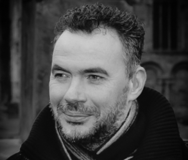 Image Description: A black and white headshot photo of Paul Miller, with short dark hair and short facial stubble, looking off into the distance and smiling.