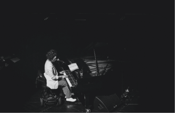 Image Description: A black and white image of Ruth Patterson in a spotlight, taken side on from the balcony above her and the room is dark. She is alone on stage at Sage Gateshead Hall 2, sat in her mobility scooter playing a grand piano and singing into a SM58 Microphone wearing a white blazer, striped black and white flares and white boots with her long curly hair tied back in a high ponytail.