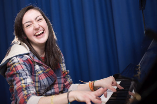 Image Description: Sarah Fisher sitting at a piano playing, whilst looking at the camera and smiling/laughing.