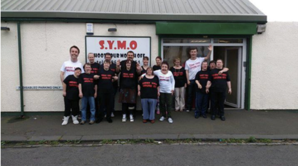 Image Description: A group photo of SYMO members, standing outside the SYMO offices. Everyone is smiling and some people are waving at the camera.