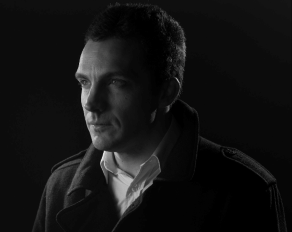 Image Description: Photo by Jon Forster. A black and white photo of Simon Taylor looking off into the distance. He is wearing a shirt and coat.