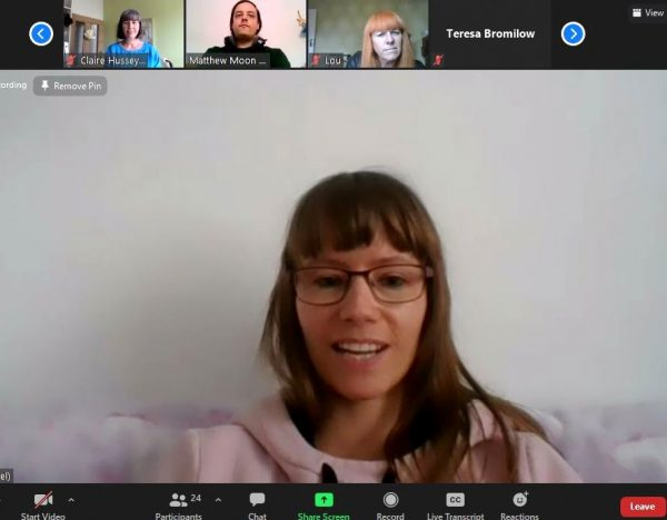 Screenshot from the online event of Becki, a white woman wearing a pink hoodie, rectangular glasses frames and she has long light brown hair with a fringe.