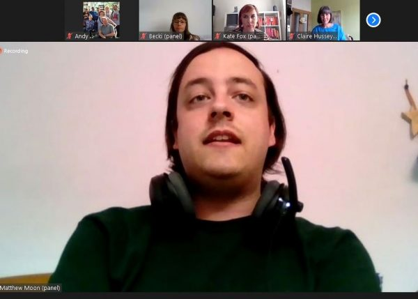 Screenshot from the online event of Matthew, a white man with medium length dark hair in a side parting. He wears a black top and has headphones round his neck.