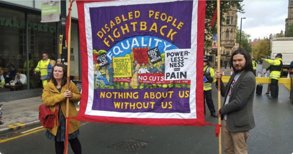 A photograph of two people walking down a street in a busy city, holding up a colourful banner which reads, 'Disabled people fight back. Equality. Nothing about us without us'.