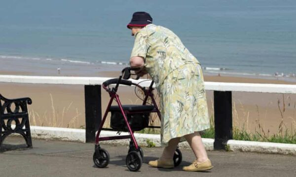 An elderly woman uses a walking frame by the sea.